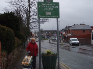 Resident Margaret Endsor with one of the locally crafted planters welcoming visitors to the village.